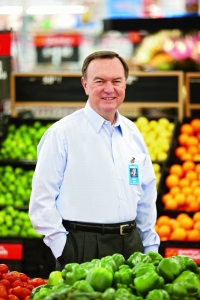 Mike Duke standing among the foods that could help save Walmart save a few billion dollars a year.